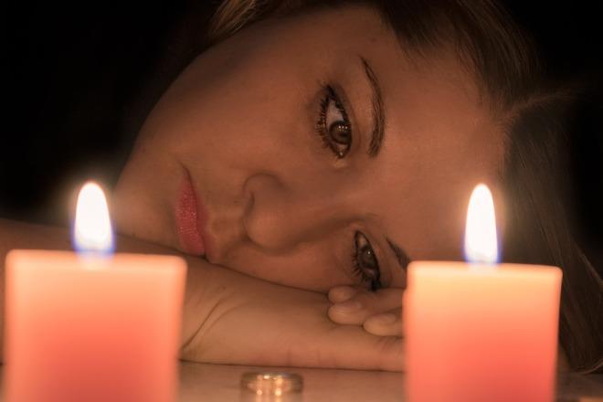 Девушка задумалась об отношениях перед свечами