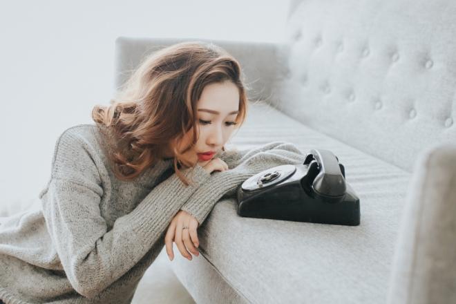 Грустная девушка пред телефоном