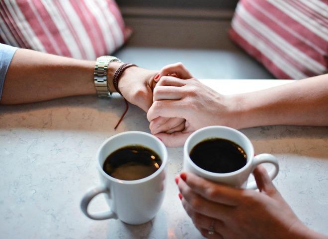 Пара держится за руки в кафе